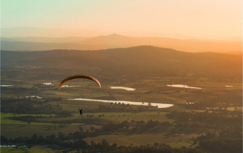 A single person in a parachute gliding in over a sunset rolling hill scene.