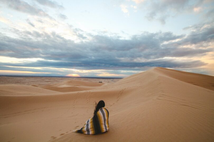 A teenage girl, wrapped in a blanket. She is sitting on a sand dune looking out at the clouds.