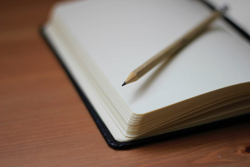 A journal is open to a blank page, and a pencil is resting on it