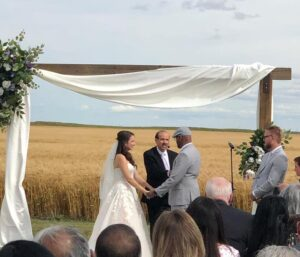 A bride and his groom hold hands in front of a group of people and a pastor.