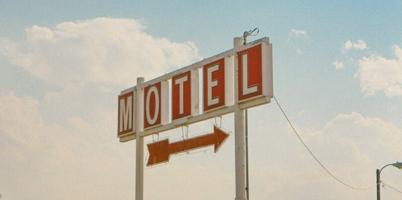 "A sign that reads ""MOTEL"" with an arrow hanging down."