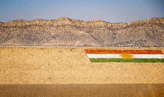 A truck drives by on a road in Iraq, and the Iraq flag can be seen.