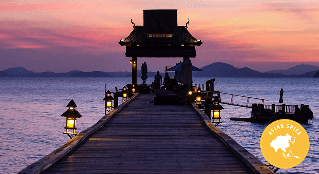 A dock out into the water in Thailand with the sun setting.