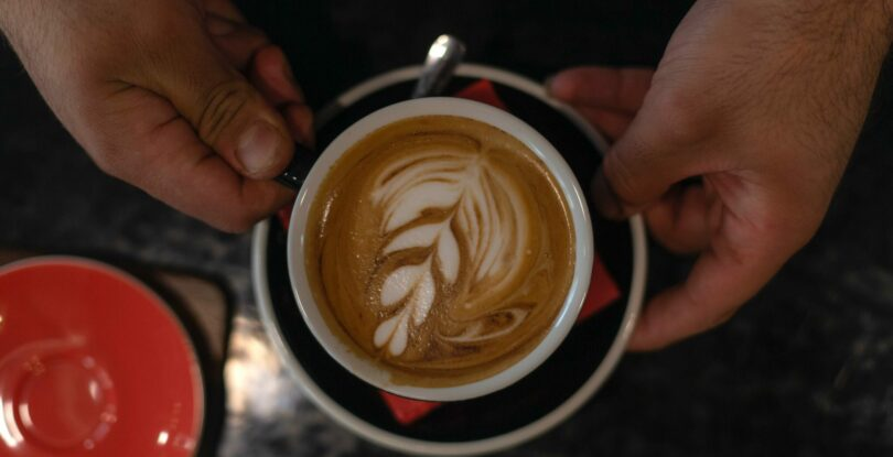 A birds-eye-view of hands holding a latte