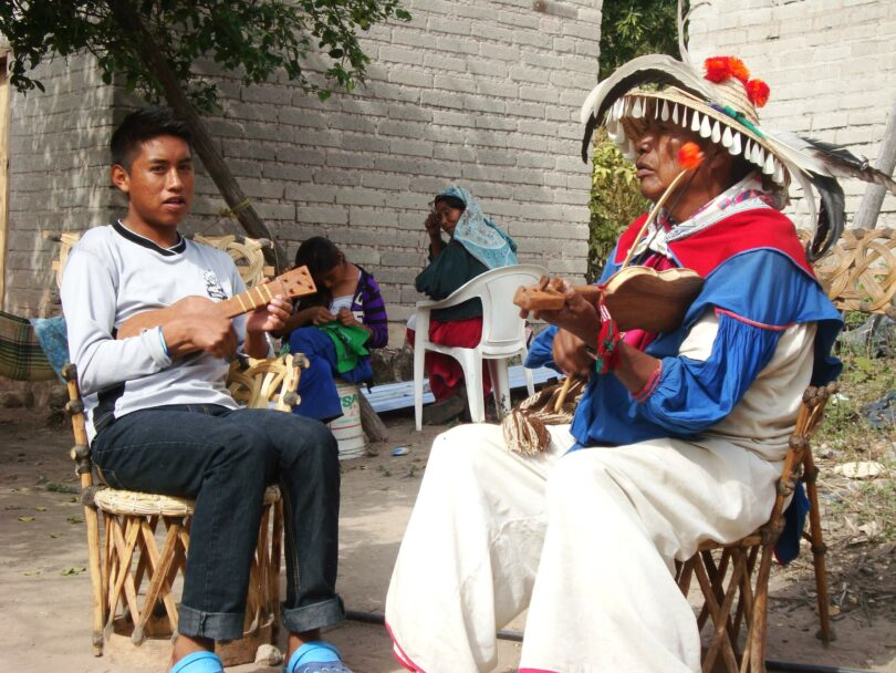 A teenage Huichol boy sits on a chair playing a small stringer instruments. An older Huichol man sits on a chair playing a small stringer instrument.