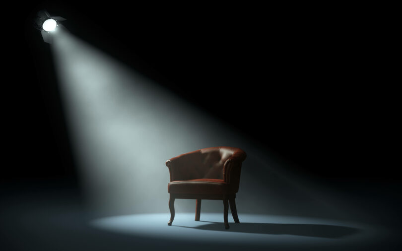 A black room with a spotlight shining on a chair.