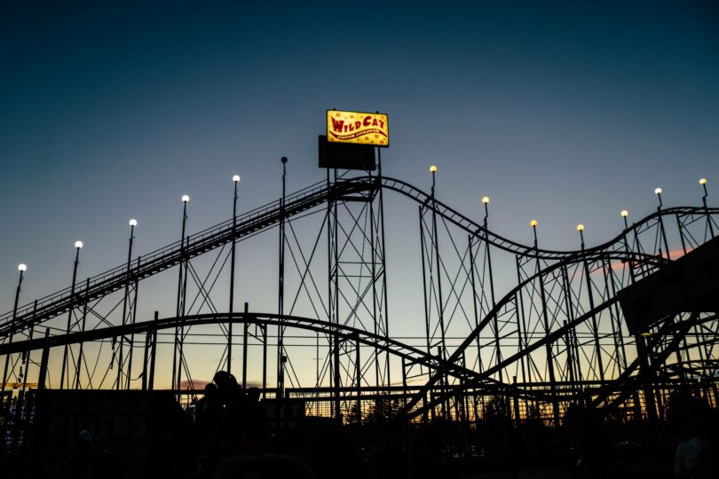 A sun sets behind a roller coaster, making the roller coaster a silhoutte