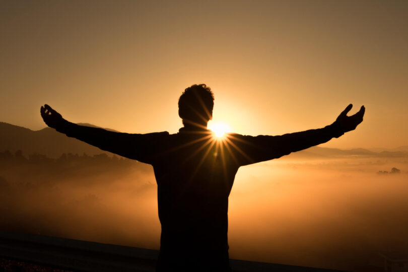 A man standing with his arms wide open facing a setting sun.