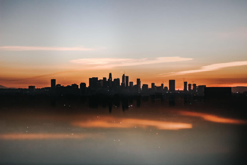 The sunsets behind the city creating a silhoutte of buildings.