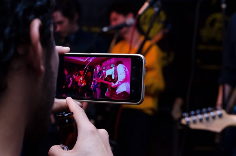 Someone holding a smartphone up recording people playing music.