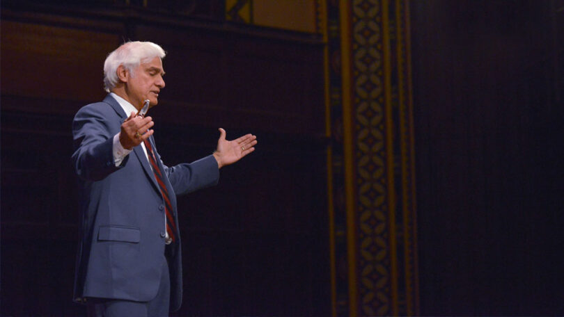Ravi Zacharias is standing with his hands open