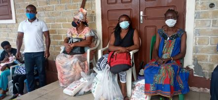 A group of people sitting with masks on and bags of groceries at their feet