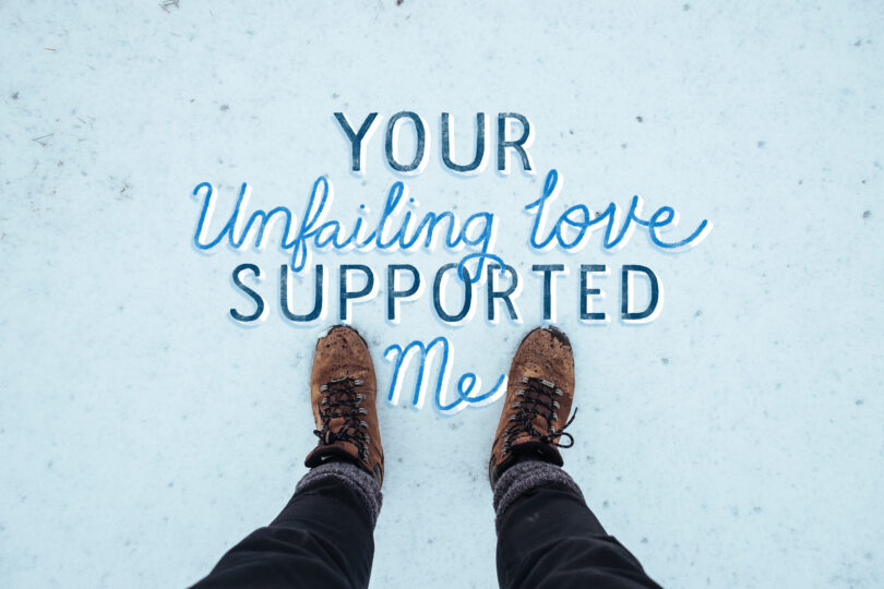"The camera is looking down at a person's feet and leggings as they stand in the snow. Hand lettering reads ""Your unfailing love supported me."""