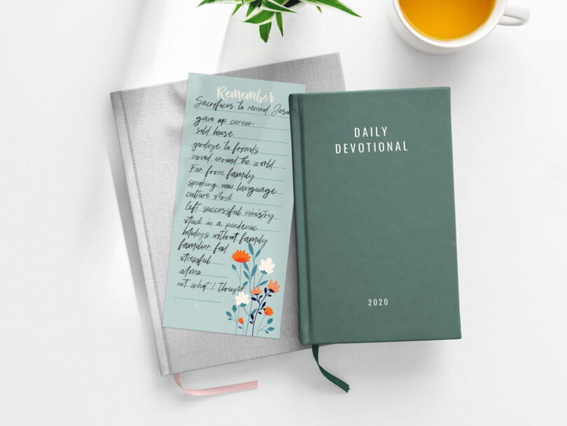 A bible and a to-do list sit on a table with some tea