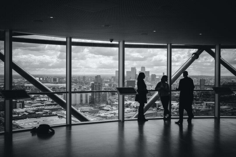 Three people in an office building overlooking a city skyline