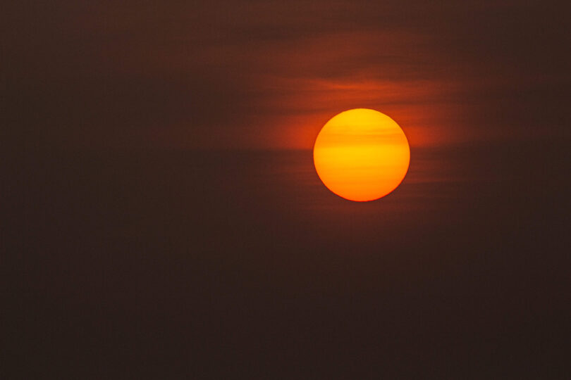 Sun setting in a misty day with a red backdrop.