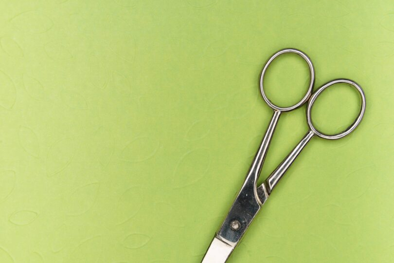 A pair of silver scissors with a green background.