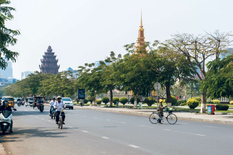 A city street in Cambodia - people are biking and a few cars are driving.