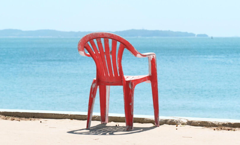 A red plastic chair is overlooking the water