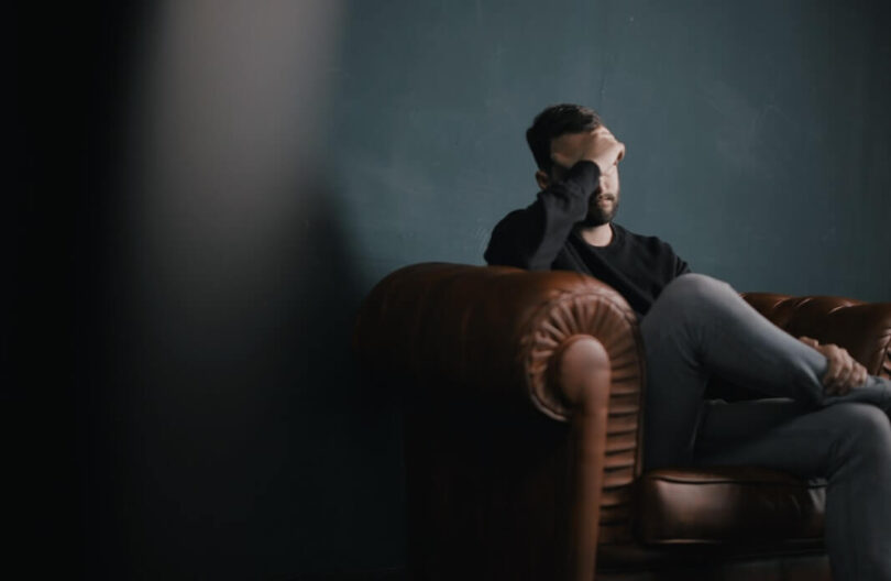 Man sitting on a couch with his head in his hands.