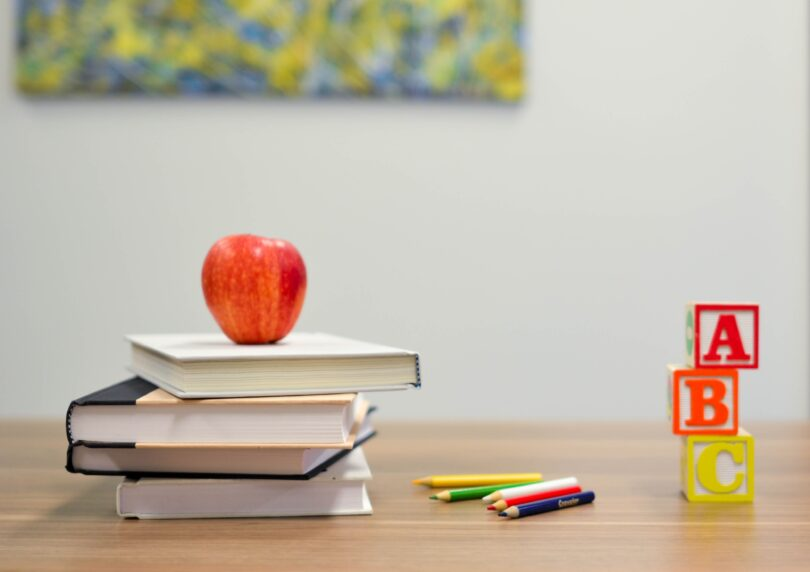 An apple sits on a pile of books on a desk.