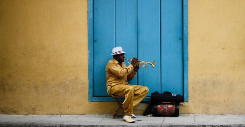A man is sitting on a stool in front of a blue door playing a trumpet.