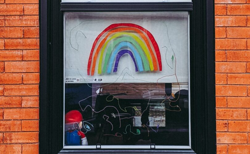 A rainbow is painted in the window of a brick building