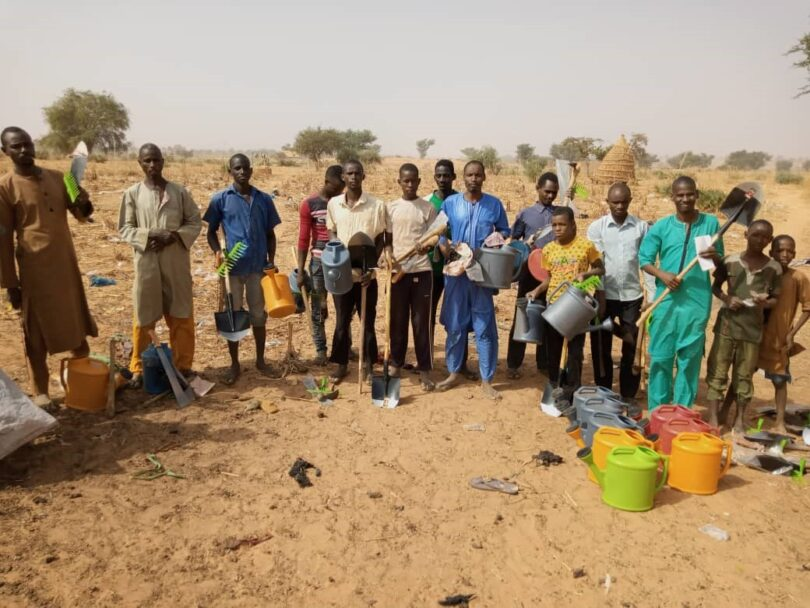A group photo of people in Niger with their new gardening tools