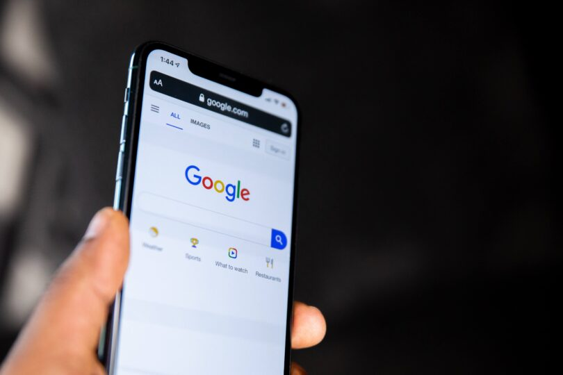 A person holding a mobile phone with a google search on the screen
