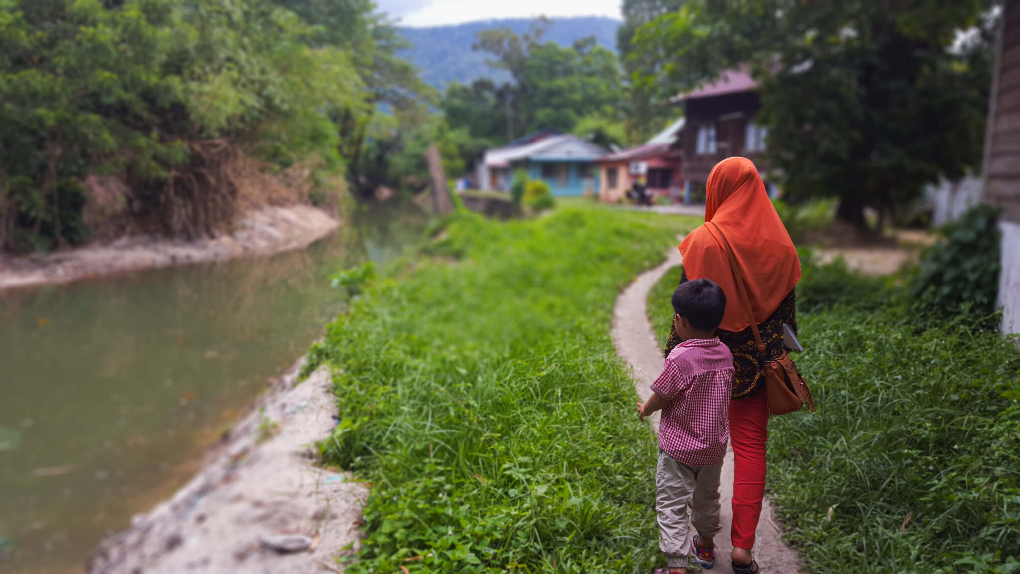 A woman and child walking to a village along a dirt path.