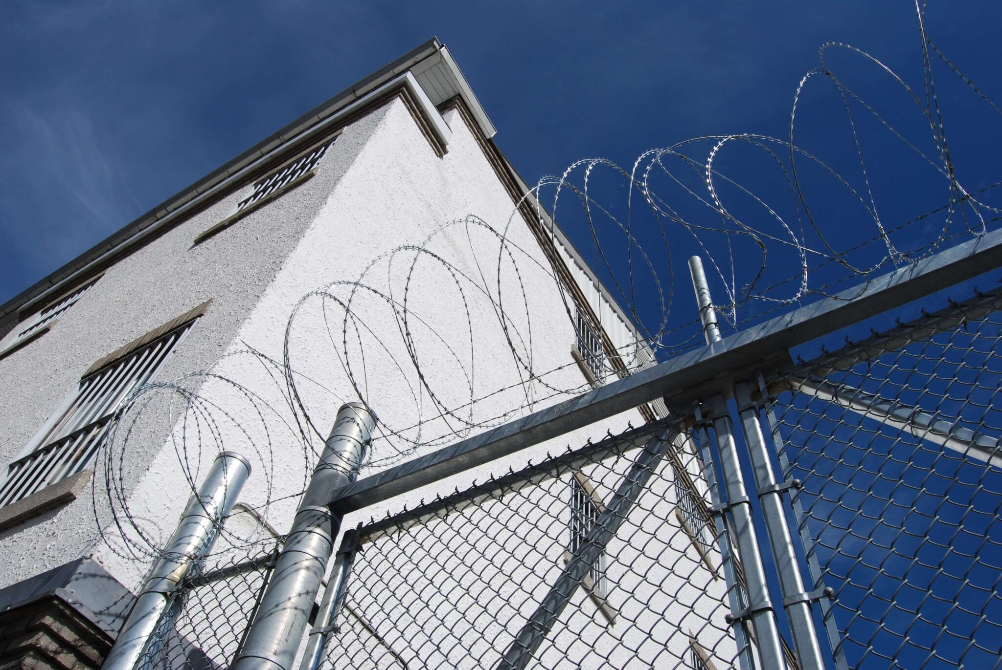 A barbed wire fence in front of a jail