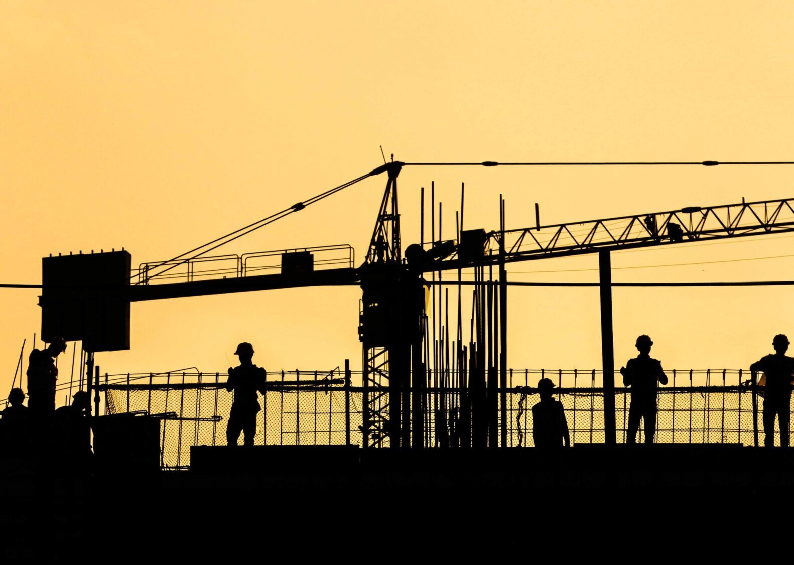 A silhouette of people at a construction site. There is a crane.