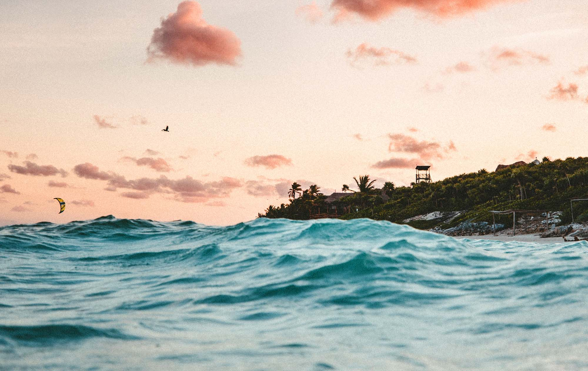 A sunset in the Caribbean. Waves in the foregroudn with the island rising from the sea.